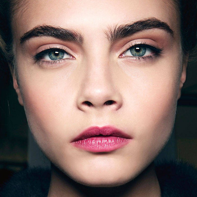 Close crop of Cara Delevingne's face with messy brows and pink lips