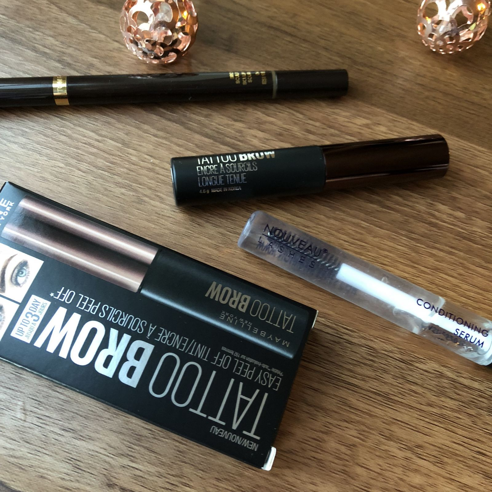 Flatlay product shot of Tom Ford Brow Sculptor in Espresso, Nouveau Lash Serum and Maybelline Tattoo brow