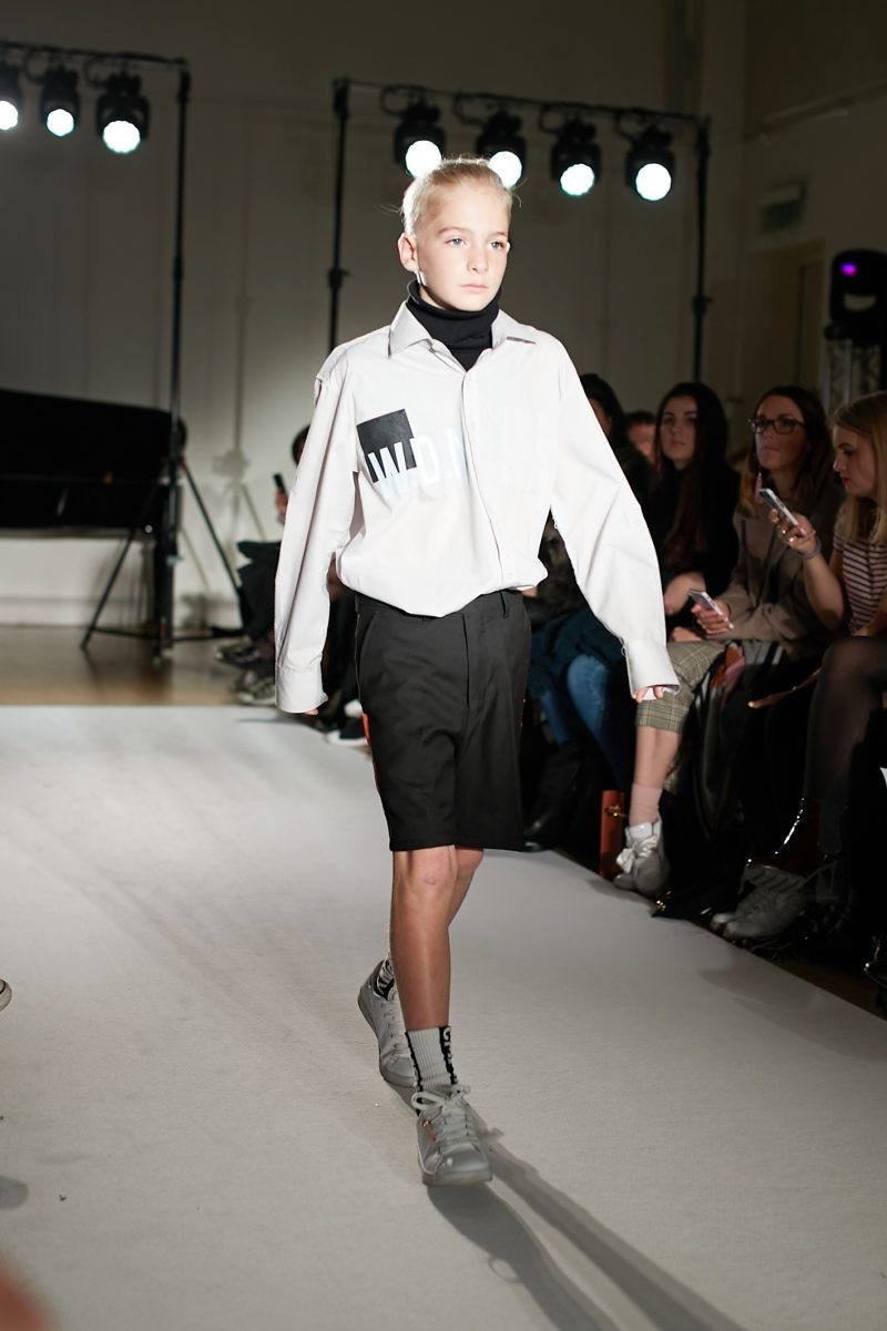 A still from the mini Mode runway show in London of a child Model wearing Alexander Evans