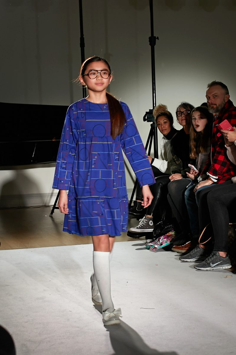 A still image of a child model walking the runway for designer Barn of Monkeys at Mini Mode london Fashion Week