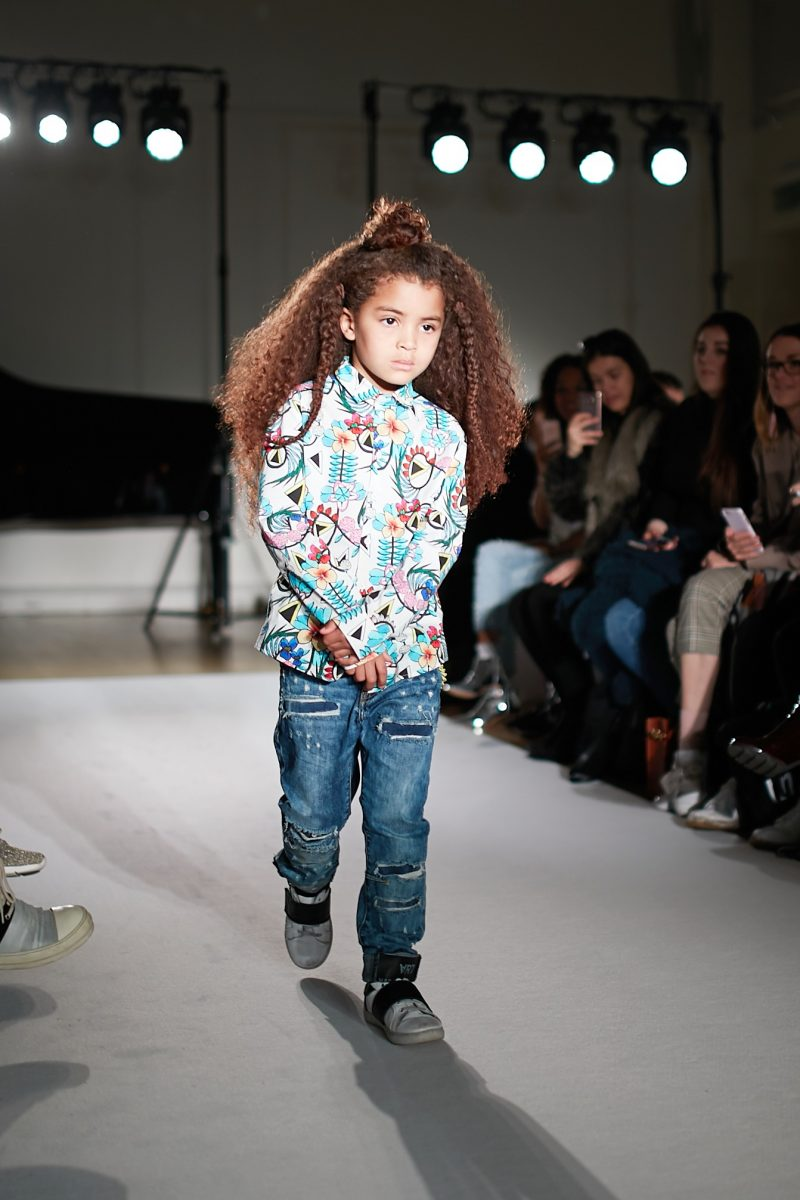 A still image of a child model walking the runway for designer Daniele Alessandrini Kids at Mini Mode London Fashion Week