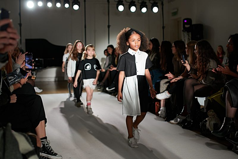 A still image of a child model walking the runway for designer loud Apparel at Mini Mode London Fashion Week