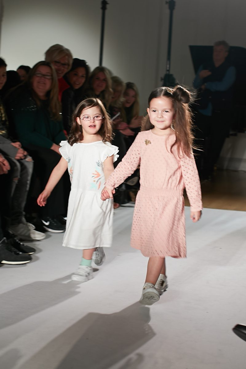 A still image of two child models holding hands on the runway for Plumeti Rain at Mini Mode London Fashion Week