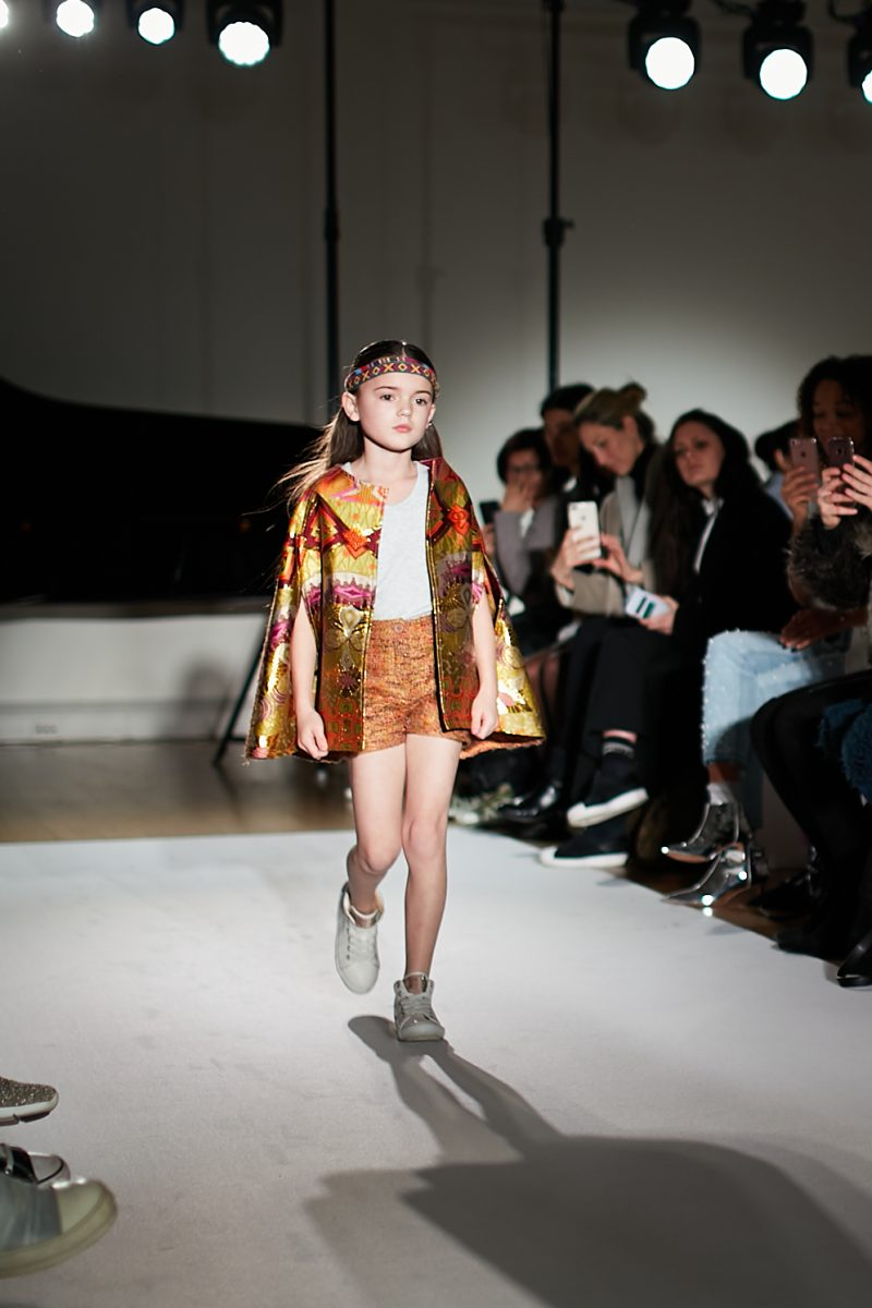 A still image of a child model walking the runway in a cape for Rebel Republic at Mini Mode London Fashion Week