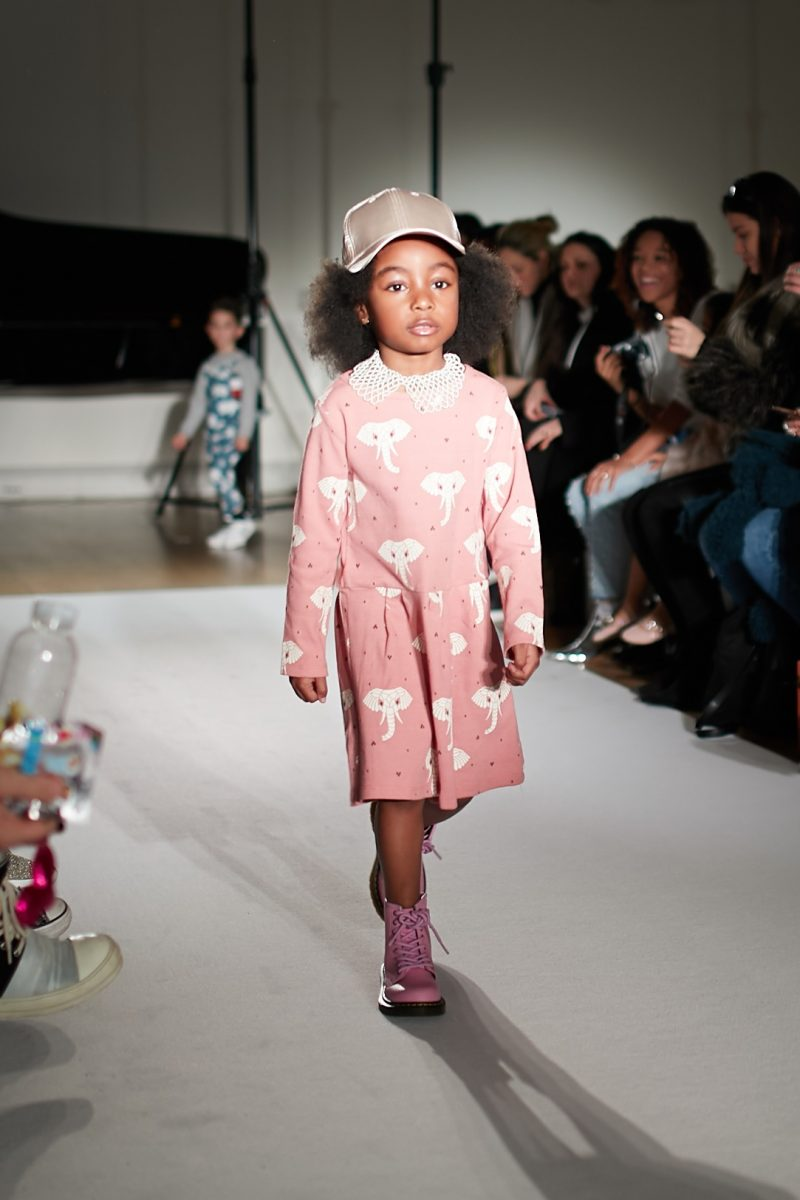 A still image of a child model walking the runway for designer Suindiatic at Mini mode London Fashion Week