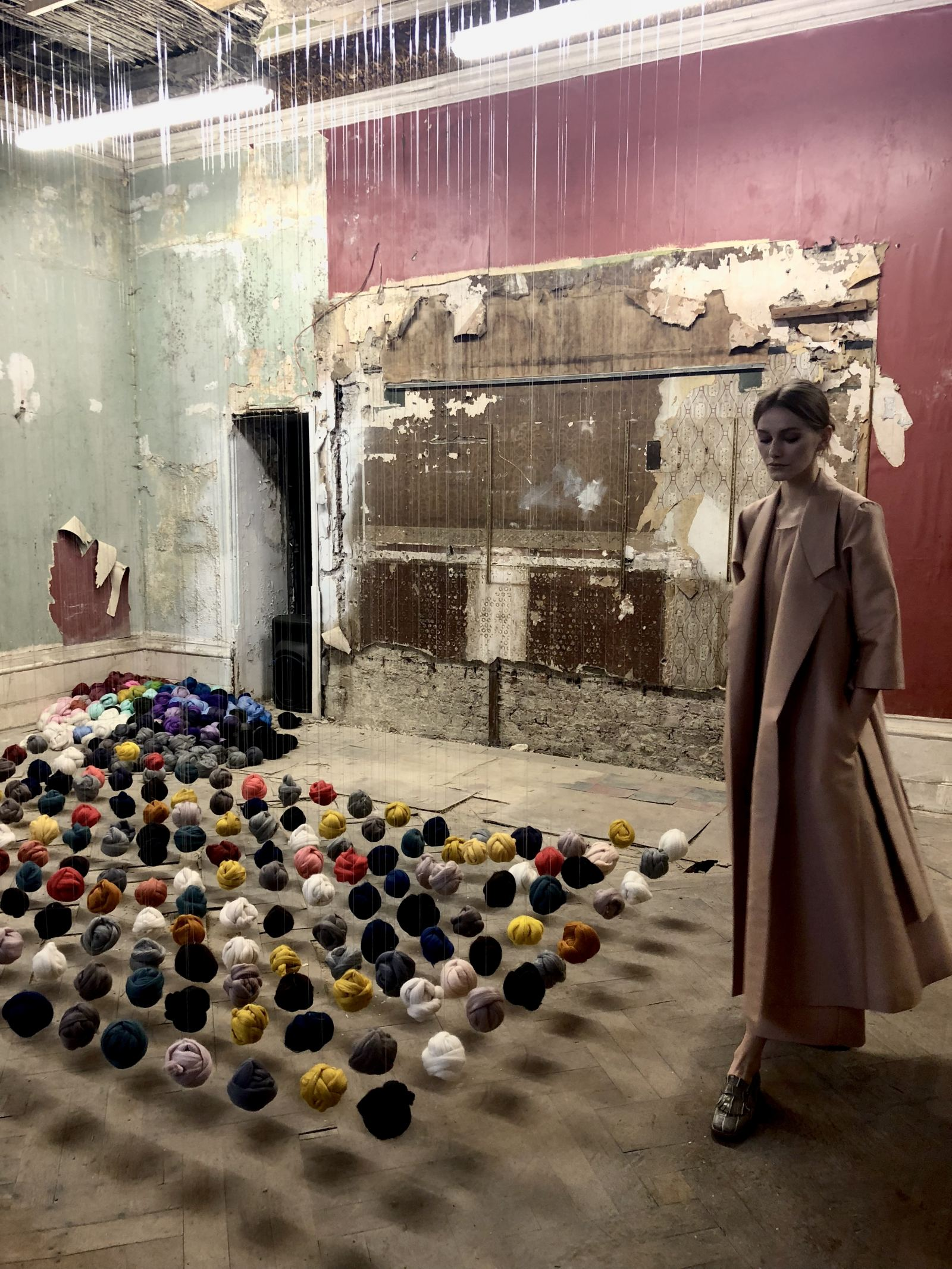 Merchant Archive FW18 A model in a pale pink coat in a room where wool balls are suspended from the ciling in a grid