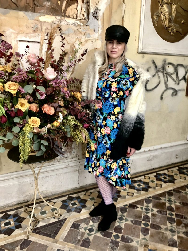 Pixie Tenenbaum wearing a floral dress & baker boy style hat at the Merchant Archive FW18 presentation at Lancaster Gare during London Fashion Week