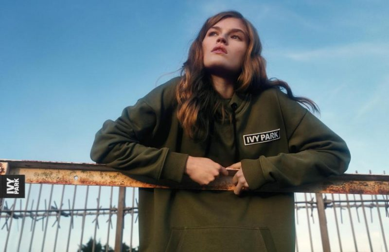 A still from the SS18 Ivy Park Campaign featuring a khaki green sports hoodie