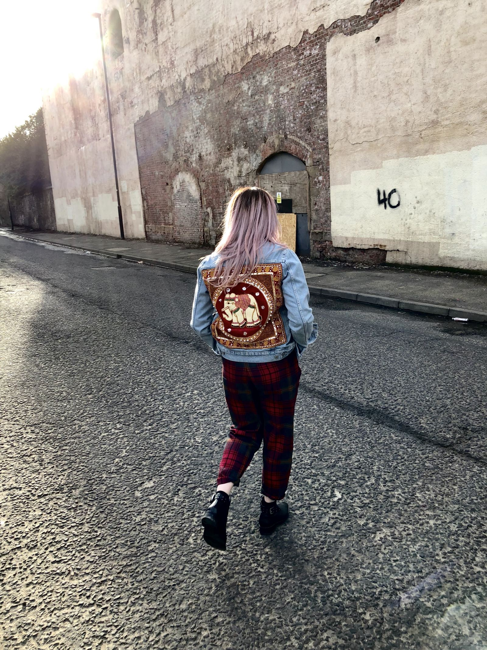 fashion blogger Pixie Tenenbaum wears a denim jacket by Flaura Rose with red elephant design on back