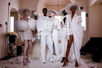 A group image of models taken after the Balmain Spring 2019 ncouture runway show in Paris in January, models are wearing all white